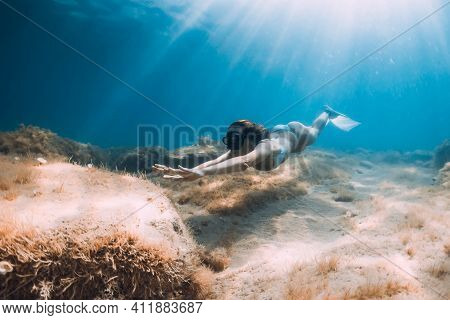 Freediver Woman With Fins Glides At Deep Sea. Freediving Underwater In Sea