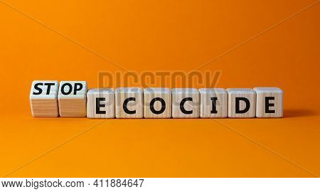 Stop Ecocide Symbol. Turned Wooden Cubes With Words Stop Ecocide. Beautiful Orange Background, Copy