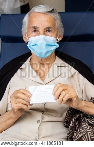 Senior Woman Holding Her Vaccination Certificate After Getting The Covid-19 Vaccine At A Vaccination