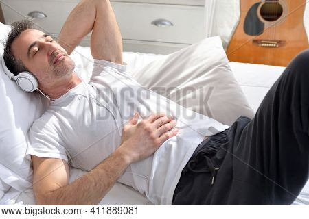 Happy And Relaxed Adult Man With Closed Eyes Dressed In Pajamas Listening To Music With White Headph