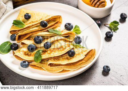 Crepes With Blueberries And Honey At Kitchen Table. Healthy Breakfast Or Snack.