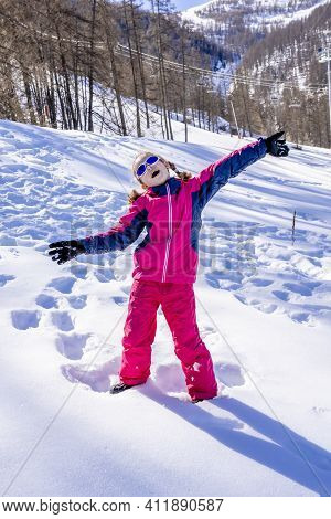 Happy Laughing Girl Wearing A Pink Ski Suit, Playing In A Beautiful Snowy Winter Forest. Girl Enjoys