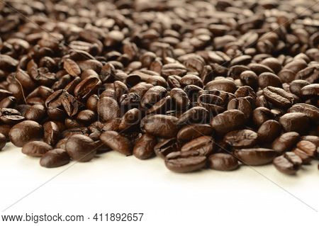 An Abundant Supply Of Freshly Roasted Coffee Beans Spilling Over A Clean White Background.