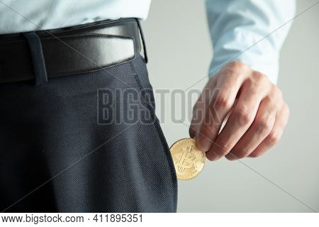 Man Hand Bitcoin In Pocket On Grey Background