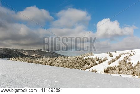 winter meadow under nice sky with clouds in Carpathian mountains in Ukraine