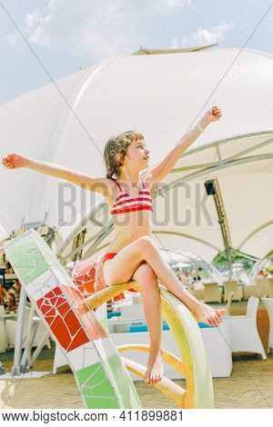 A Little Girl Is Resting In The Summer In The Aqua Park. Child Active Summer Vacation In Summer.