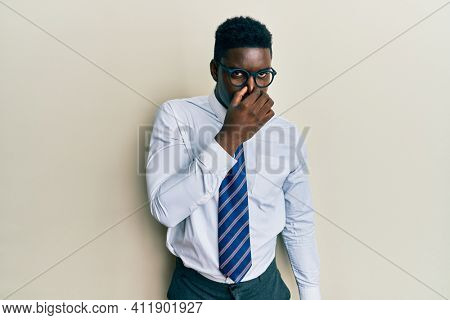 Handsome black man wearing glasses business shirt and tie smelling something stinky and disgusting, intolerable smell, holding breath with fingers on nose. bad smell