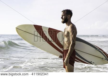 Surfer Holding His Surfboard On The Beach - Hipster Man Standing On The Beach And Waiting Big Waves