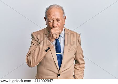 Senior caucasian man wearing business suit feeling unwell and coughing as symptom for cold or bronchitis. health care concept.
