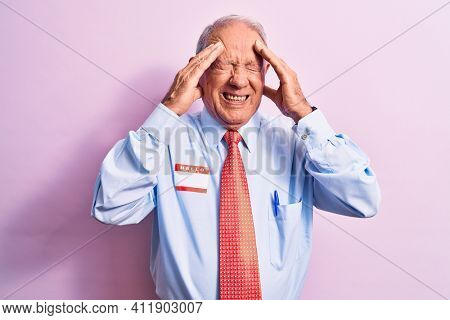Senior handsome grey-haired businessman wearing tie and shirt with name presentation sticker with hand on head, headache because stress. Suffering migraine.
