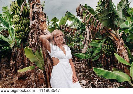 A Girl On A Banana Plantation On The Island Of Mauritius, A Banana Farm On A Tropical Island, A Girl