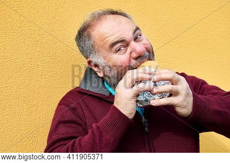 Funny Bearded Mature Man Eating Sandwich On The Street Against A Yellow Wall. Man Hungry Like A Wolf