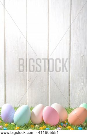 Easter Greeting Card, Invitation Background. Easter Eggs In A Row On Spring Grass And White Wooden B