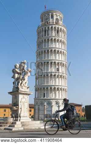 Pisa, Italy - March 10, 2021 - Woman On Bicycle With Protective Mask Passes In Front Of The Leaning