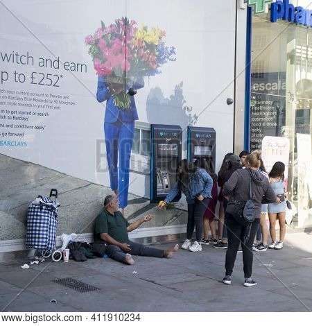 London, Uk - 20 September 2020, A Young Girl Gives Alms To A Romanian Beggar Sitting Near The Barcla