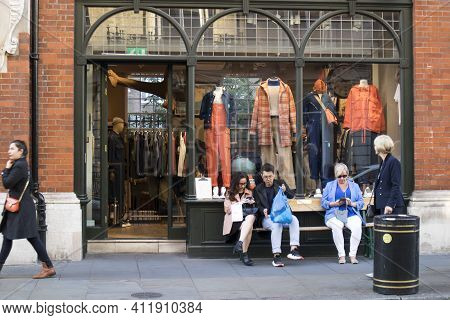 London, Uk - 20 September 2020, People With Shopping After Shopping Sit Outside The Store On Covent