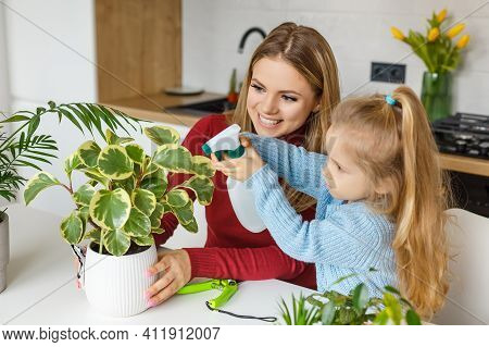 Little Daughter And Mother Spraying And Cleaning Houseplants At Home. Concentrated 3 Year Old Kid He
