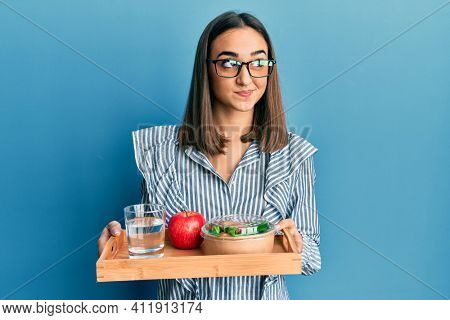 Young brunette girl holding tray with healthy lunch smiling looking to the side and staring away thinking.