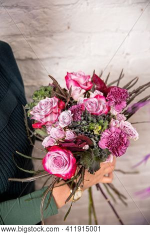 Florist's Workplace. The Florist Makes A Bouquet Of Roses, Carnations And Eucalyptus, Adding Flowers