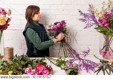 Florist Workplace On The Background Of A White Brick Wall. The Florist Makes A Bouquet Of Roses, Car
