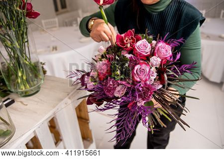 Florist's Workplace In A Loft Space. An Experienced Florist Composes A Bouquet Of Roses, Carnations