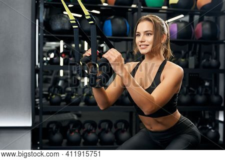 Close Up Of Attractive Young Fitness Woman Doing Cardio Exercise With Trx System In Modern Gym. Conc