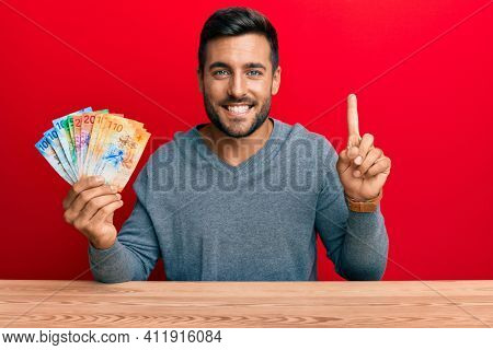 Handsome hispanic man holding swiss franc banknotes smiling with an idea or question pointing finger with happy face, number one