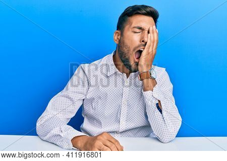 Handsome hispanic man wearing business clothes sitting on the table yawning tired covering half face, eye and mouth with hand. face hurts in pain.