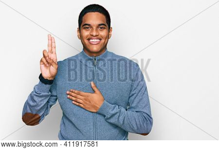 Young handsome hispanic man wearing casual sweatshirt smiling swearing with hand on chest and fingers up, making a loyalty promise oath