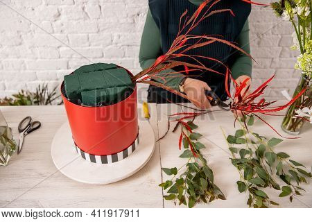 Florist Workplace On The Background Of A White Brick Wall. An Experienced Florist Has Prepared The B