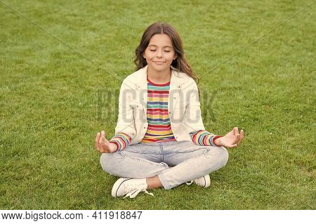 Kid Meditating In Yoga Pose On Grass. Child In Lotus Pose On Green Grass. Concept Of Calm And Medita