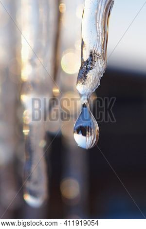 An Icicle And A Drop Of Meltwater In The Rays Of The Sunset Close-up. Thaw And Snowmelt. Bright Vert