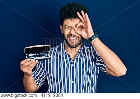 Young arab man with beard holding glasses in eyewear case smiling happy doing ok sign with hand on eye looking through fingers
