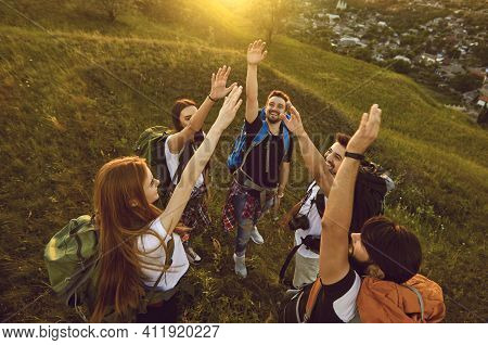 High Angle Of Team Of Happy Tourists Reaching Out For High Five While Hiking On Grassy Hill