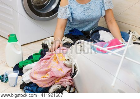 Unhappy Woman In Bathroom With Pile Of Dirty Clothes And Different Laundry Detergents. Hard Work, Di