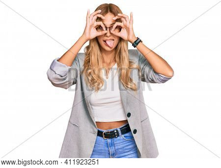 Beautiful blonde young woman wearing business clothes doing ok gesture like binoculars sticking tongue out, eyes looking through fingers. crazy expression.