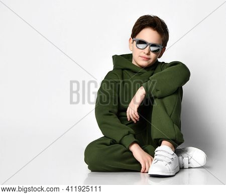 Boy Teenager In Sportswear And Sunglasses Sitting On A Gray Background. Boy In A Green Suit Sit Near