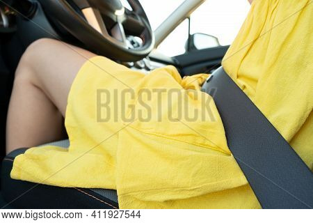 Close Up Of Woman Driver In Yellow Summer Dress Wearing Seatbelt Driving A Car.