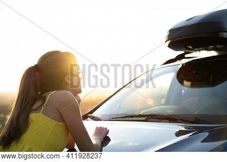 Yong Happy Woman Standing Near Her Car Enjoying Sunset View Of Summer Nature. Travel And Getaway Con