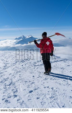 Ski Patroller On Snow Caped Mountain Is Walking Against Sun With A Red Rescue Jacket And A Shovel On