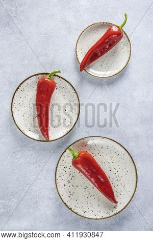 Fresh Raw Sweet Red Pepper Kapi With Water Drops In White Ceramic Plates, Three Peppers On Gray Tabl