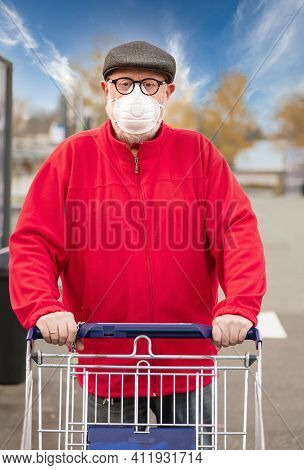 A Senior Man Wears An N95 Respirator Mask While Pushing A Shopping Cart Outside Of A Grocery Store.
