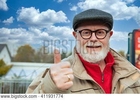 Outdoor Portrait From A Optimistic Senior In Winter Cloth Shows Thumb Up