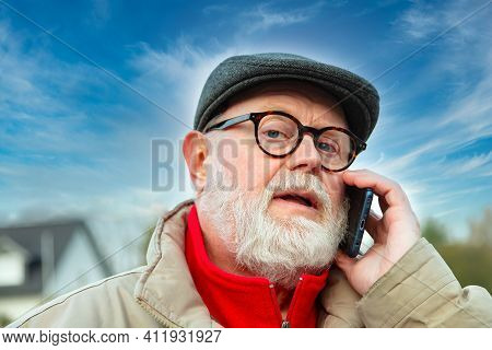 Man With Cap In Winter Clothes Using Cell Phone Outdoor.
