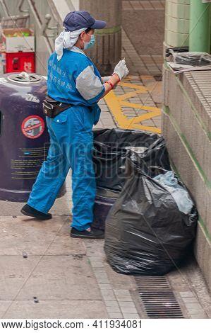 Hong Kong Island, China - May 14, 2010: Closeup Of Female Trash Collector In Blue Garb And Facemask