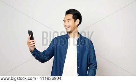 Video Call Conference, Happy Asian Man Having A Video Chat On Mobile Phone While Standing On Grey Ba