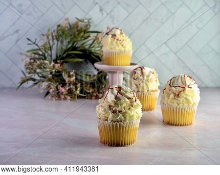 White Cupcakes With White Frosting Swirled High And Curled White Chocolate With Red Raspberry Drizzl