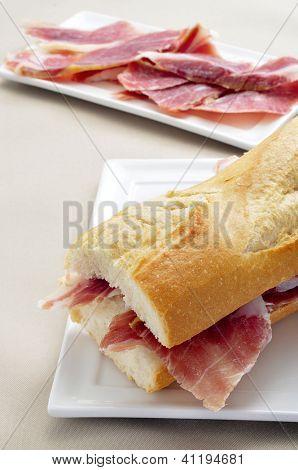 closeup of a spanish serrano ham sandwich in a plate