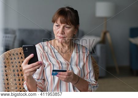 Smiling Senior Woman Shopping Online Or Pays Utility Bills Through The Personal Account Of The Onlin