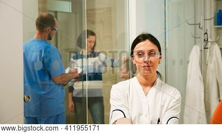 Pediatric Dentist Looking At Camera Smiling, While Man Assistand Speaking With Patients About Dental
